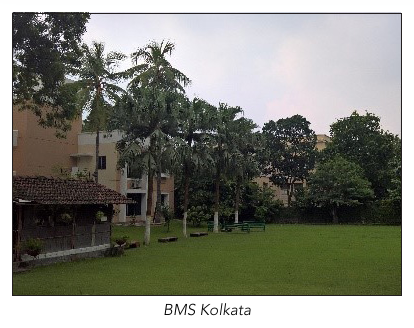View of BMS Kolkata: 2 storey building behind palm trees and lawn in foreground