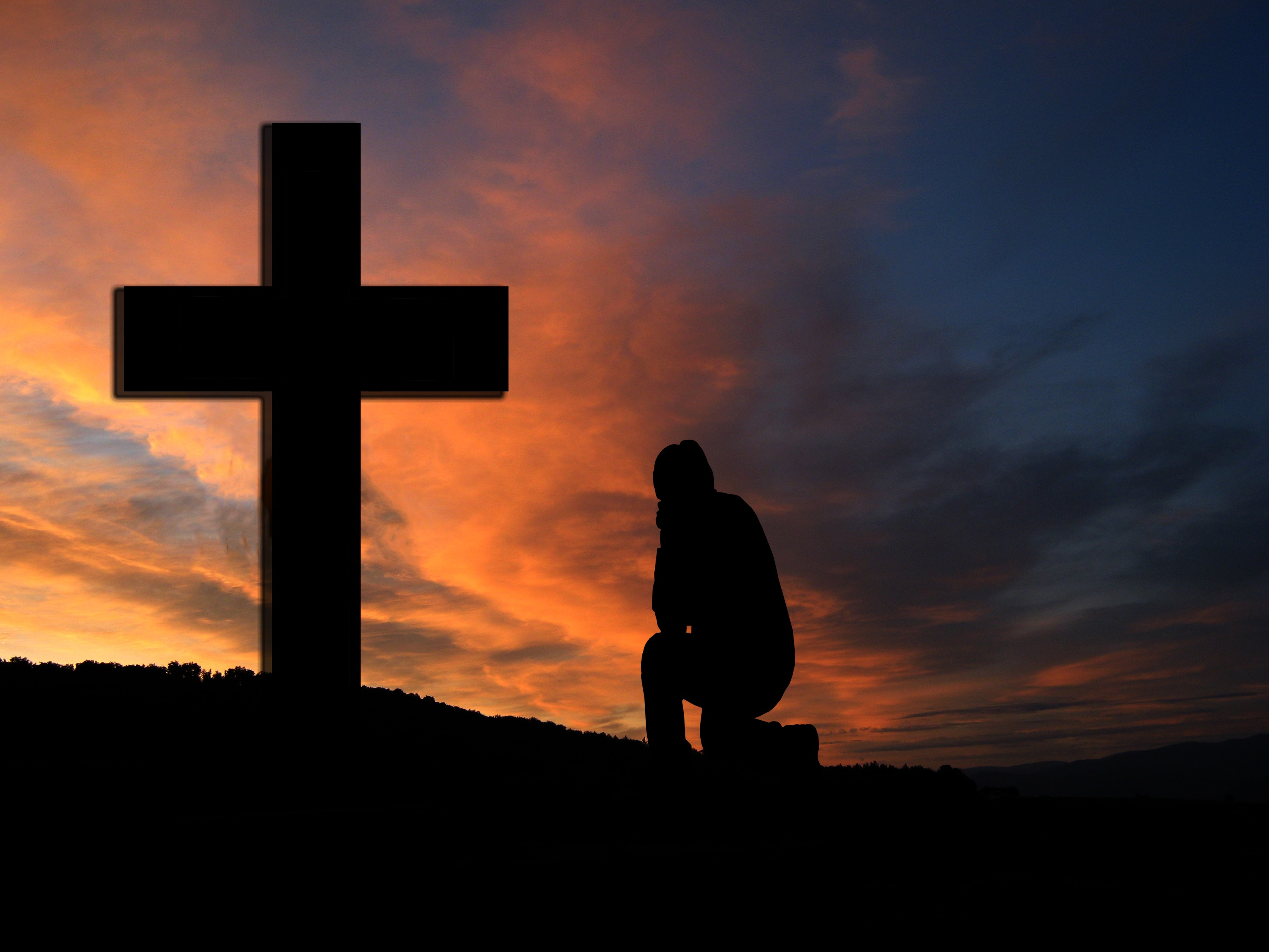 Silhoetted figure kneels at cross against sunset background