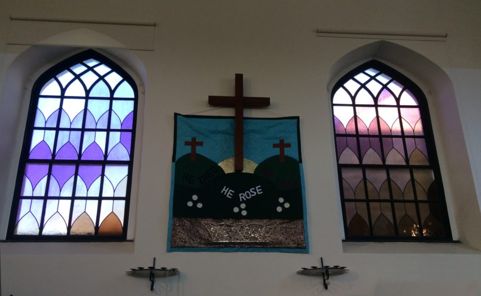 Banner made by craft group hanging between the windows and behind the cross in the Sanctuary